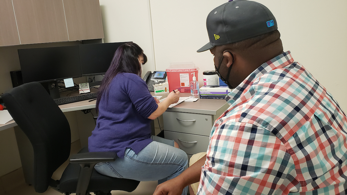 Lisa McAllister completes paperwork for a vaccine